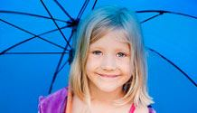 A young blonde girl with blue eyes smiling underneath a royal blue umbrella
