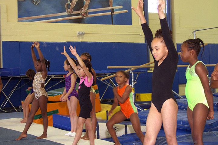 A group of gymnasts practicing gymnastics with arms raised and feet pointed