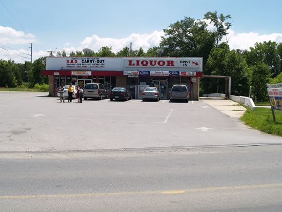 Liquor Store with cars parked in front and people standing by cars